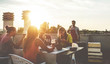 canvas print picture Young friends having barbecue party at sunset on penthouse patio