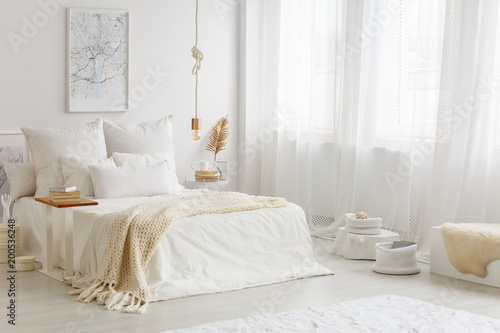 Foto  Beige blanket on white bed