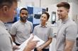 Engineering Team Meeting On Factory Floor Of Busy Workshop