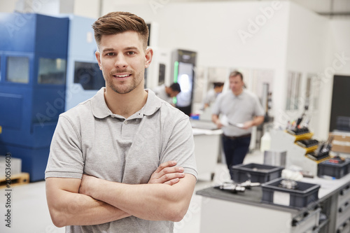 Portrait Of Male Engineer On Factory Floor Of Busy Workshop