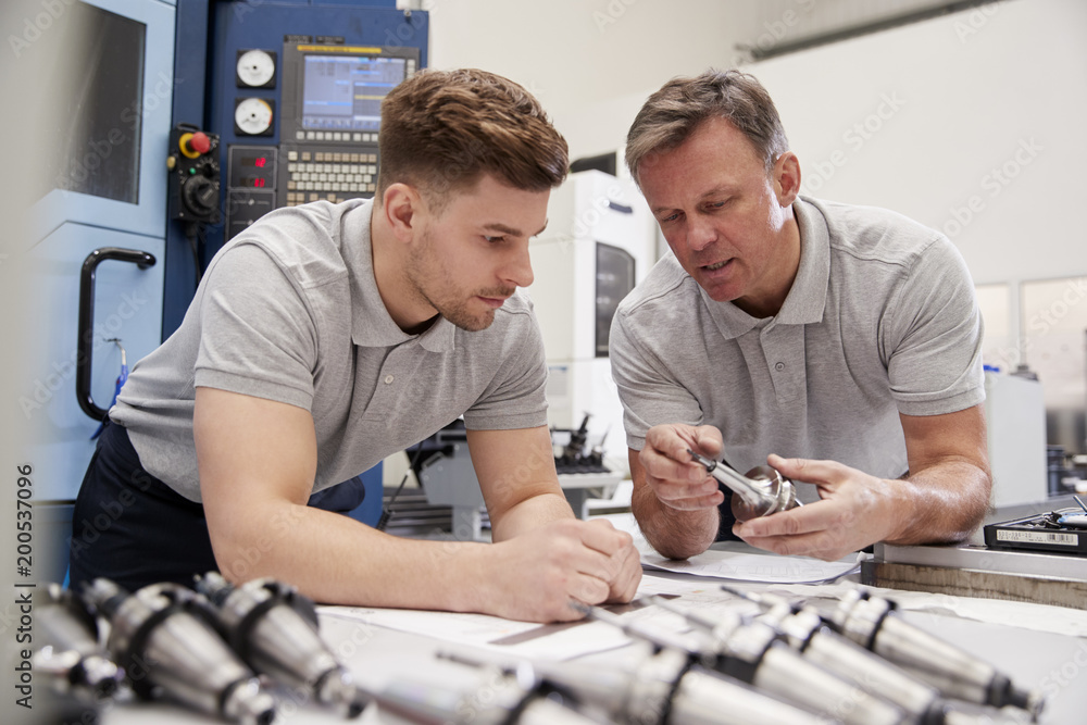 Fotografie, Obraz Engineer Showing Apprentice How To Measure CAD Drawings