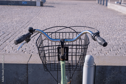 A Riders eye viewpoint of a set of curved handlebars and a basket on a green bic Wallpaper Mural