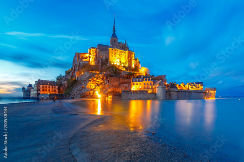 Fotografie, Obraz  Famous Mont Saint Michel Illuminated in the evening blue hour with reflection at