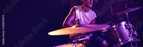 Photo Singer playing drums while performing in nightclub