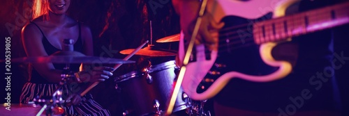 Man playing guitar with female drummer in nightclub - 200539805