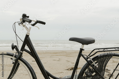 Fotografie, Obraz  Day-time side view to the black citybike with rack by the sea without driver