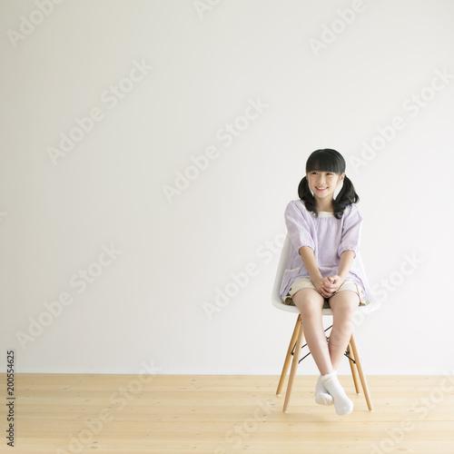 椅子に座り微笑む女の子