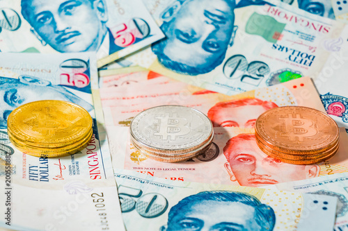 Singapore Dollar banknotes and Bitcoin Cryptocurrency coins