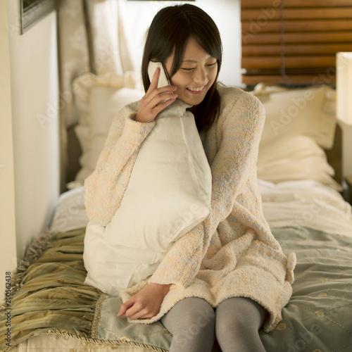 ベッドに寝転びスマートフォンで電話をする女性