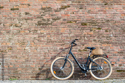 Foto op Canvas Fiets Black retro vintage bicycle with old brick wall.