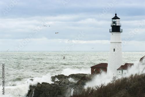 Foto op Aluminium Vuurtoren Surf Crashes All Around Maine Lighthouse as Sun Breaks Through Clouds