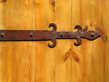 Old Fashioned Ornamental Metal Hinge Screwed To A Wooden Door