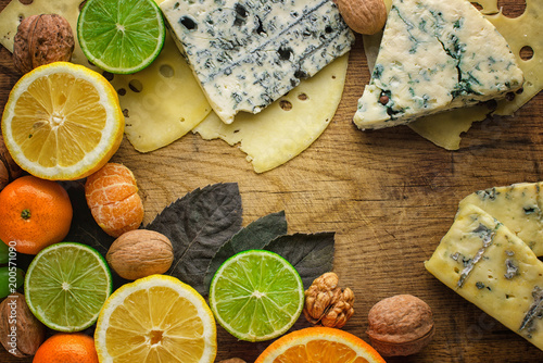 Cheese plate: Emmental, Camembert cheese, blue cheese,, hazelnuts, honey, grapes on wooden table