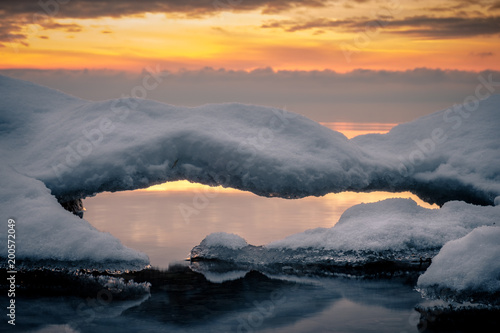 Fotobehang Grijs winter image of a lake at sunset with a bridge of snow in the foreground