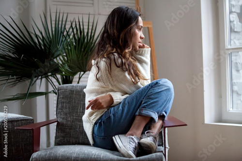 Fotografia Sad thoughtful teen girl sits on chair feels depressed, offended or lonely, upse