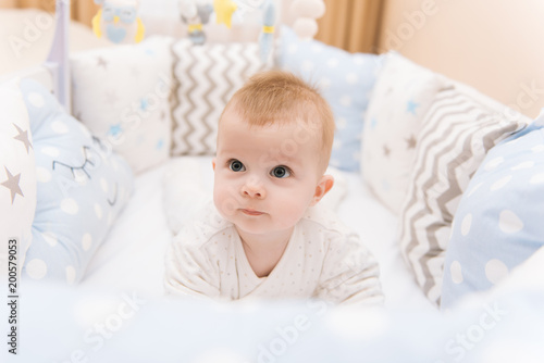 Photo Cute baby lies on her stomach in a white round bed