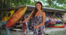 Smiling Latina Woman Standing Outside With Bike Surfboard Rentals In Background