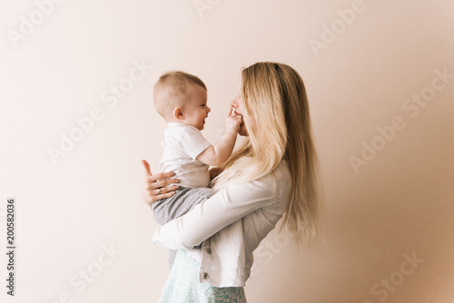 Obraz Mother playing with baby boy, happy family having fun indoor, cheerful sweet kid portrait, mom and child, healthy toddler, lifting throwing carrying holding up game - fototapety do salonu