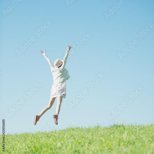 草原でジャンプをする女性の後姿