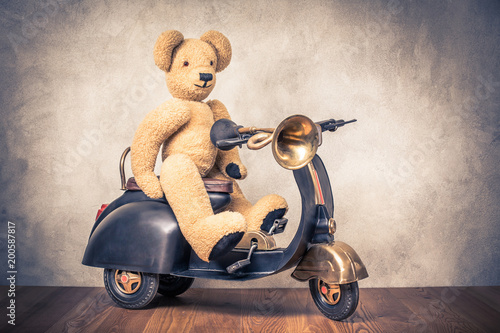 Foto op Canvas Scooter Teddy Bear sitting on old black retro toy pedal scooter trike with classic klaxon in front concrete textured wall background. Vintage style filtered photo