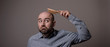 Leinwanddruck Bild - confused bald man with hair brush