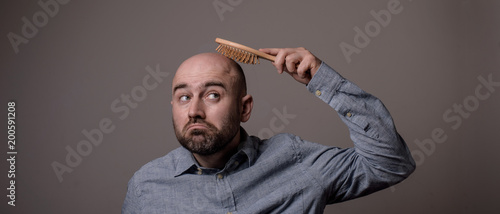 Stampa su Tela confused bald man with hair brush