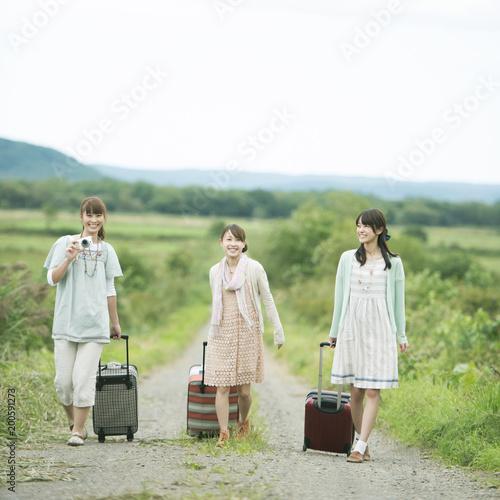旅行鞄を持ち一本道を歩く3人の女性 Buy This Stock Photo And