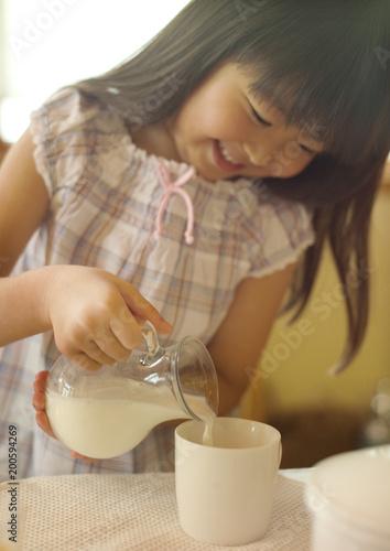 牛乳をカップにそそぐ女の子