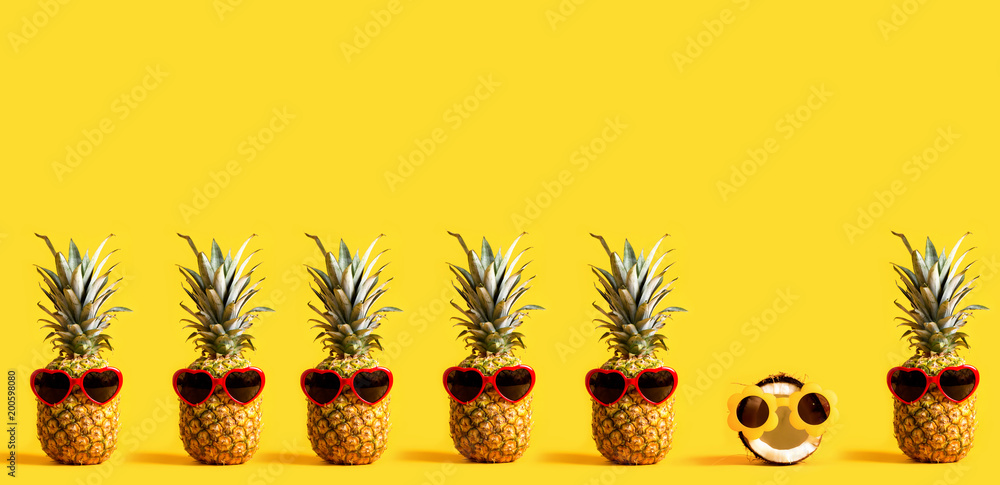 Fototapety, obrazy: Series of pineapples and a coconut wearing sunglasses on a yellow background