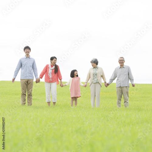 草原で手をつなぐ3世代家族