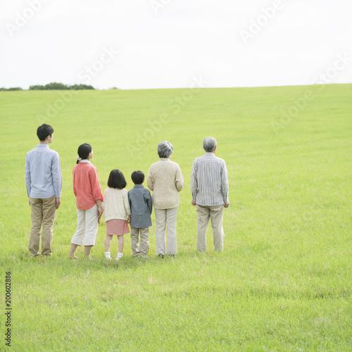 草原に立つ3世代家族の後姿