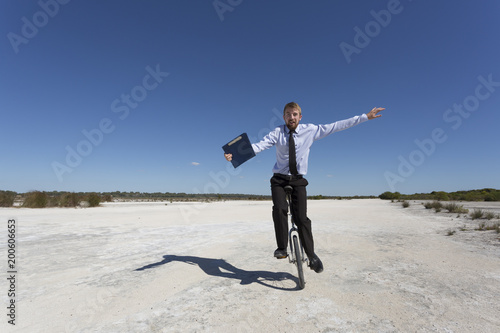 Fototapety, obrazy: A young business man riding a unicycle, a humorous concept.
