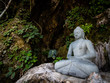 Buddha statue with stone and leaves