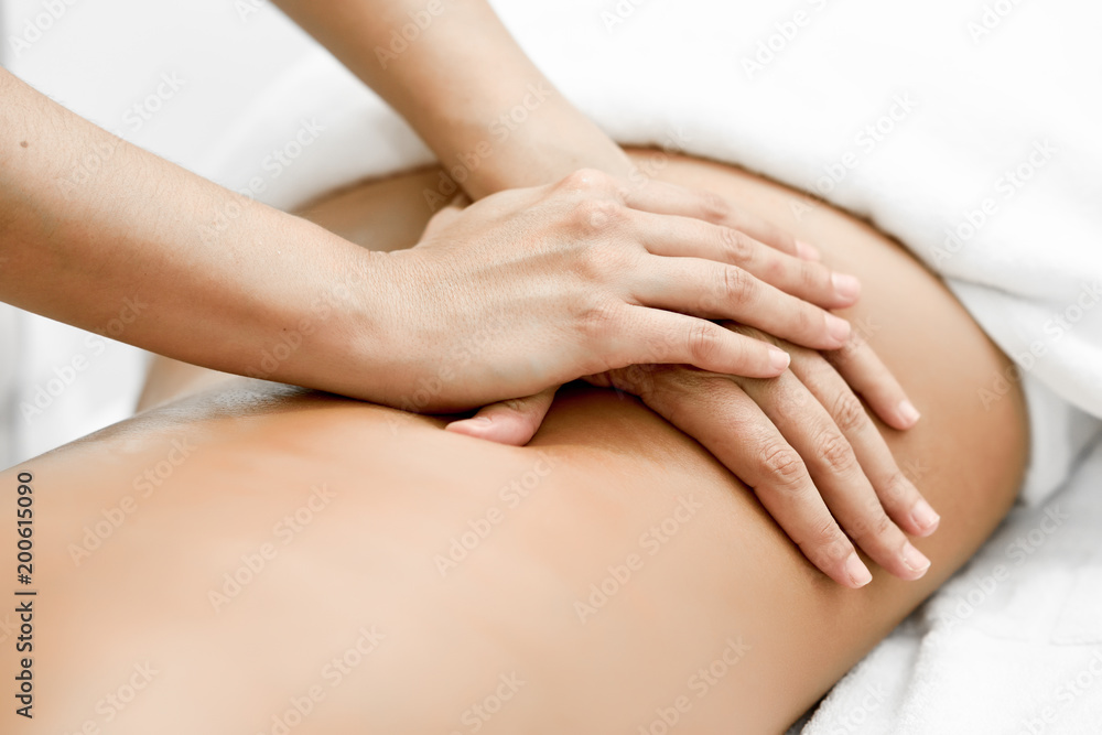 Fototapeta Young woman receiving a back massage in a spa center.