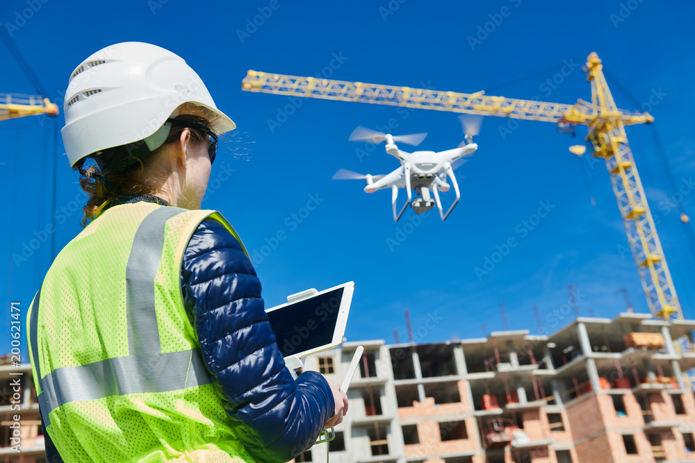 Fototapeta Drone inspection. Operator inspecting construction building site flying with drone