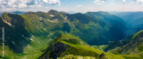 Foto op Aluminium Nachtblauw panorama of Fagarasan mountain ridge in summertime. lovely landscape with cliffs and grassy hills over the valley. TransFagarasan road in the left corner runs through the valley in to the distance