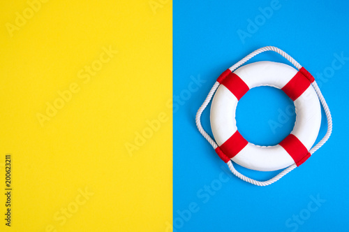 Fényképezés Lifebuoy on a yellow and blue background with blank space for text