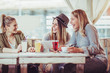 canvas print picture - Female friends enjoying in conversation and drinking coffee in cafe and using digital tablet.
