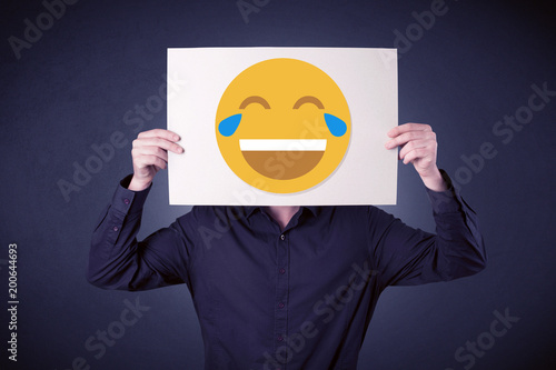 City on the water Young businessman hiding behind a laughing emoticon on cardboard