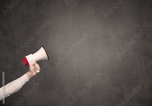 Tuinposter Fietsen Caucasian arm holding megaphone with plain grunge background