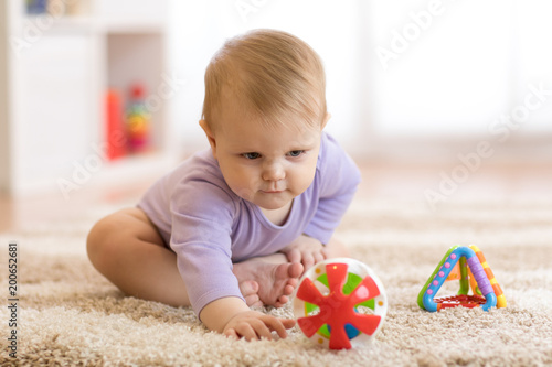 Deurstickers Kamperen Baby girl playing with colorful toys sitting on a carpet at home