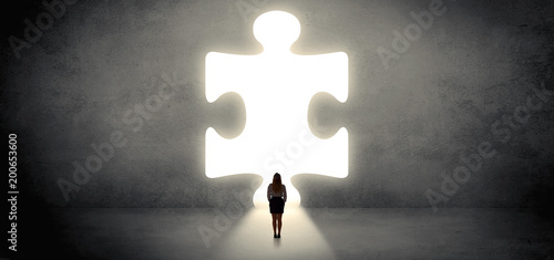 Obraz Woman standing and looking to a big puzzle piece