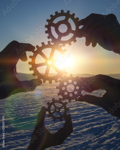 Pinturas sobre lienzo  four people businessman hold gears puzzle on sunset background