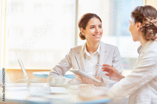 Happy businesswoman listening to explanation of her colleague during presentatio Wallpaper Mural