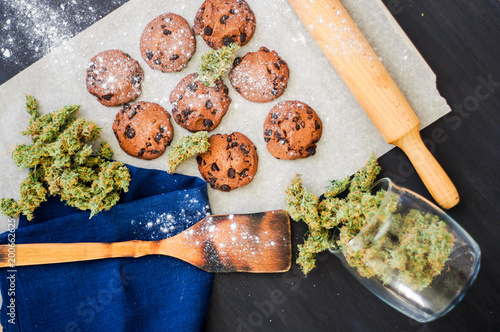 Cookies with cannabis and buds of marijuana on the table. top viewConcept of cooking with cannabis herb. Treatment of medical marijuana for use in food, On a black background top view