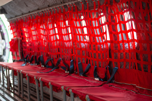 Photo red seat with seatbelt for paratrooper or airborn forces in military transport a