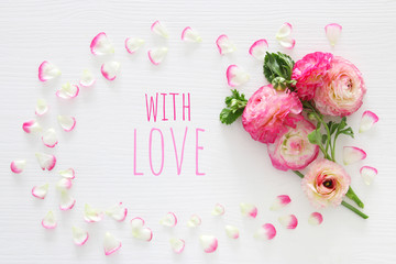 Image of delicate pastel pink beautiful flowers arrangement over white wooden background. Flat lay, top view.