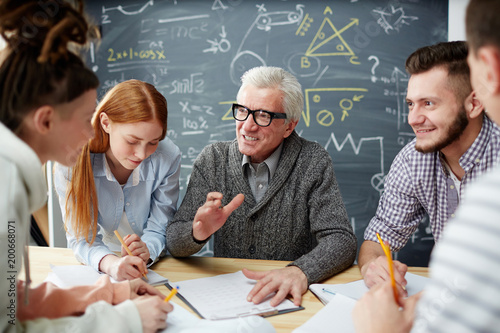 Foto Confident teacher explaining details of his lecture points to group of students