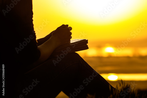 Photo silhouette of the hands of woman praying to God in the nature witth the Bible at