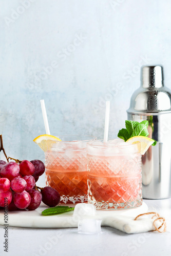 Fotografía  pink alcoholic cocktail of fresh ripe grapes in a shaker with ice, lemon and mint